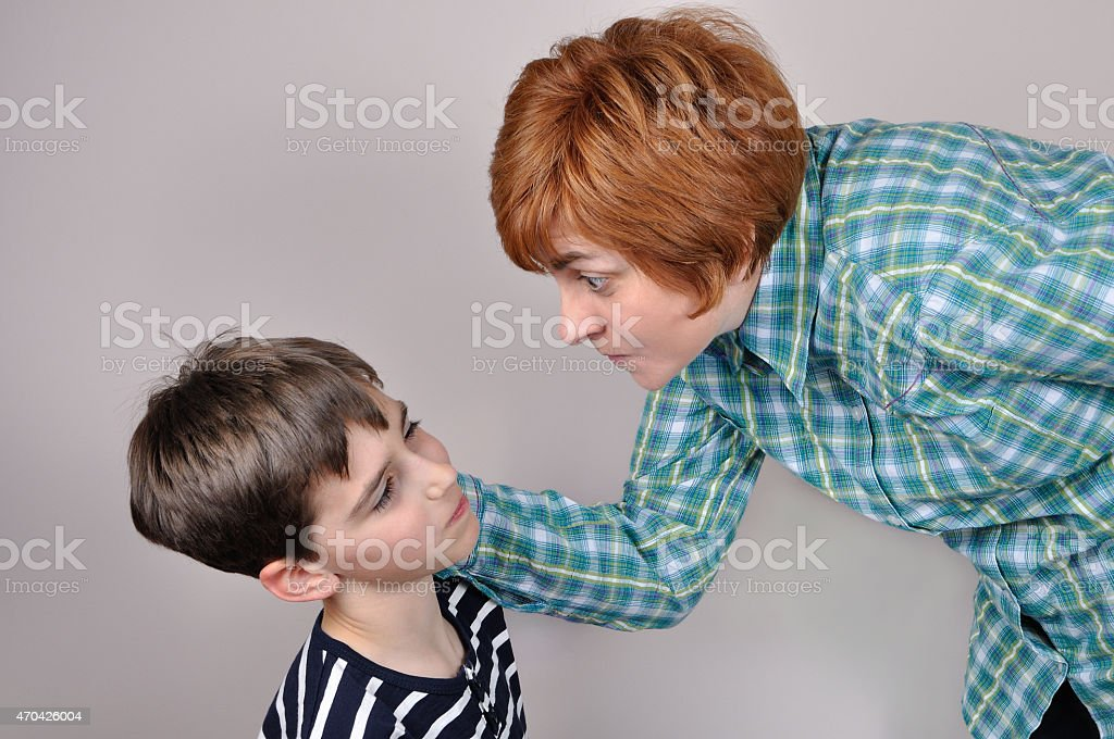 Woman scolding a scared young boy stock photo