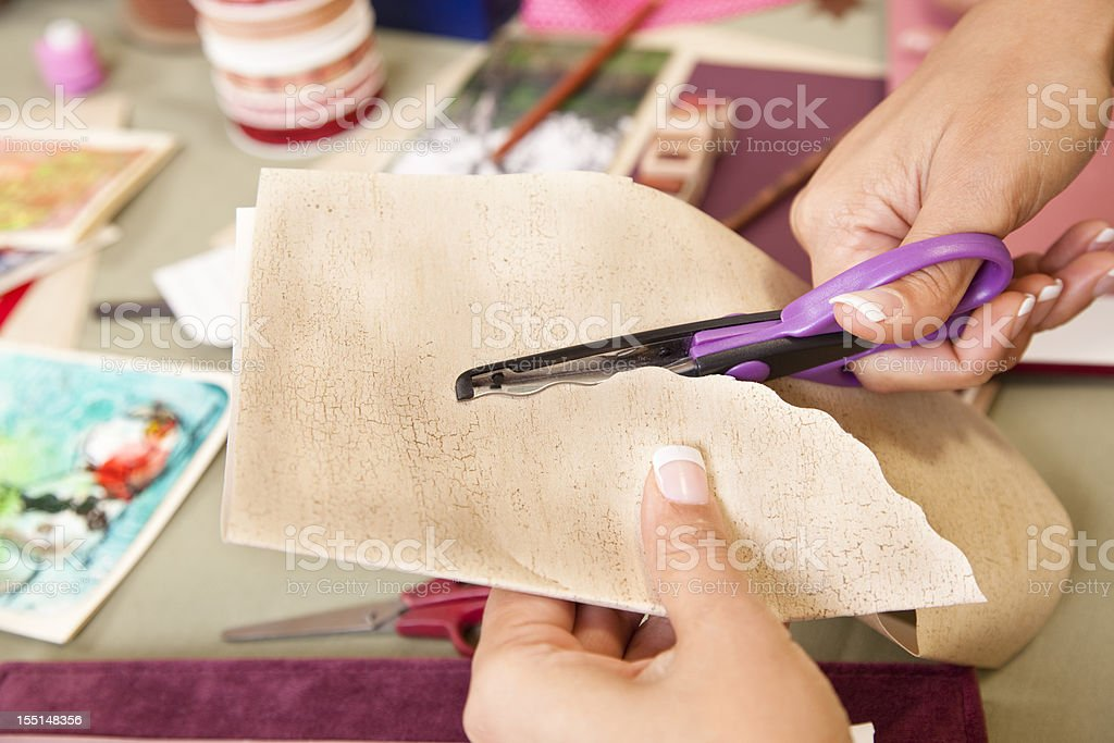 Woman scrapbooking, cutting background papers. Hobby, art, crafts. stock photo