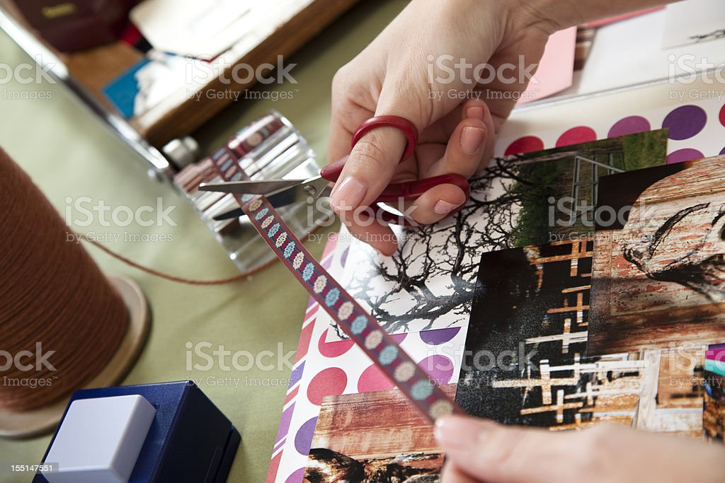 Woman scrapbooking, cutting trim and arranging photos. Craft, hobby. stock photo