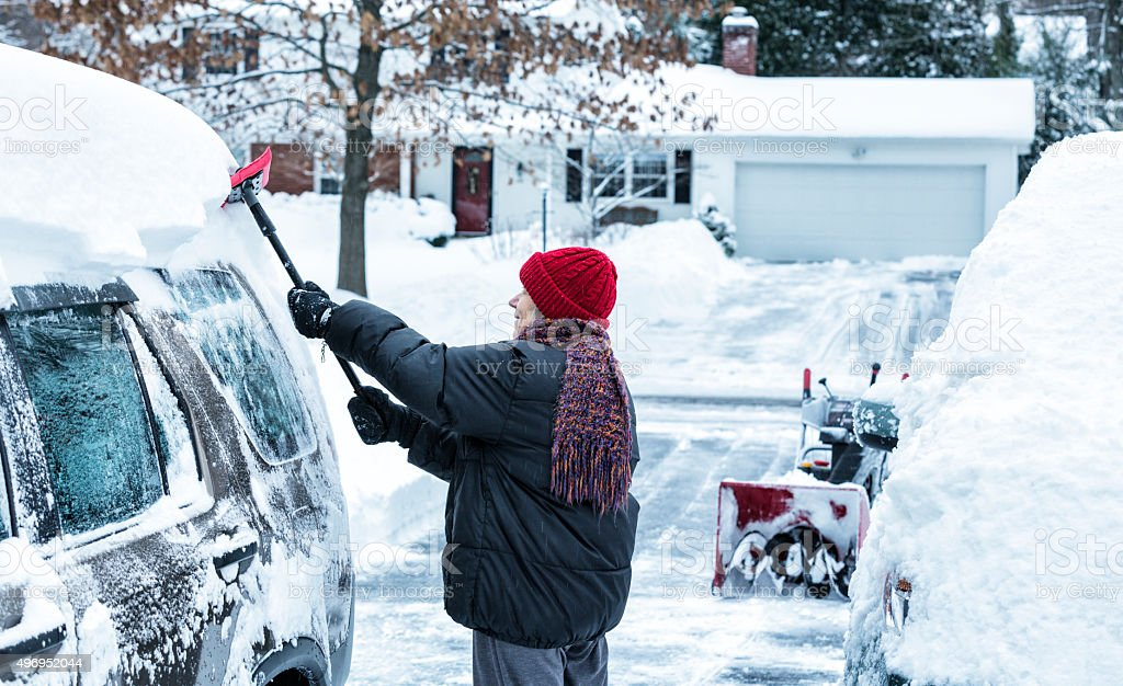 Woman Scraping Deep Snow Off Car Roof After Winter Storm stock photo