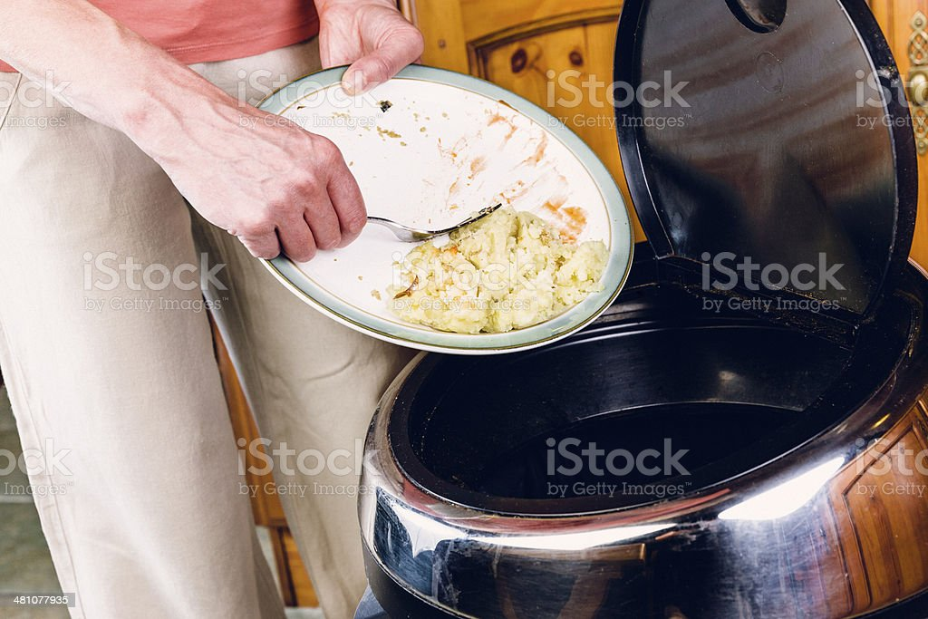 Woman scraping food leftovers into a bin stock photo