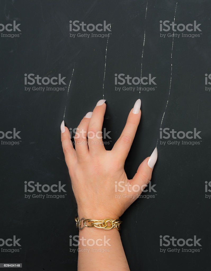 Woman scratches the blackboard with her long nails stock photo