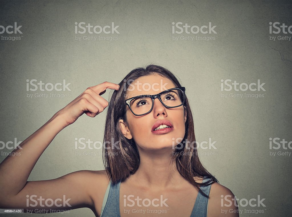 woman scratching head thinking daydreaming about something stock photo