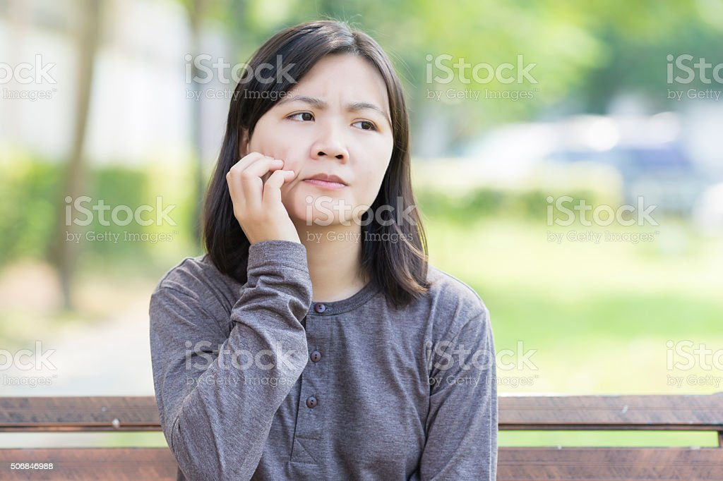 Woman Scratching Her Face at Park stock photo