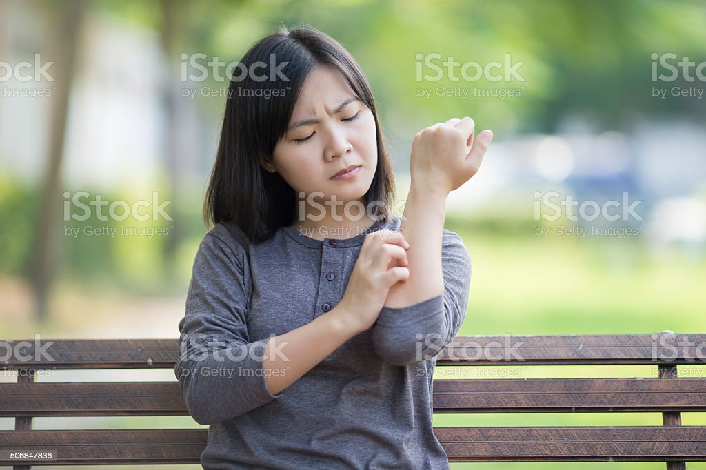 Woman Scratching Her Hand stock photo