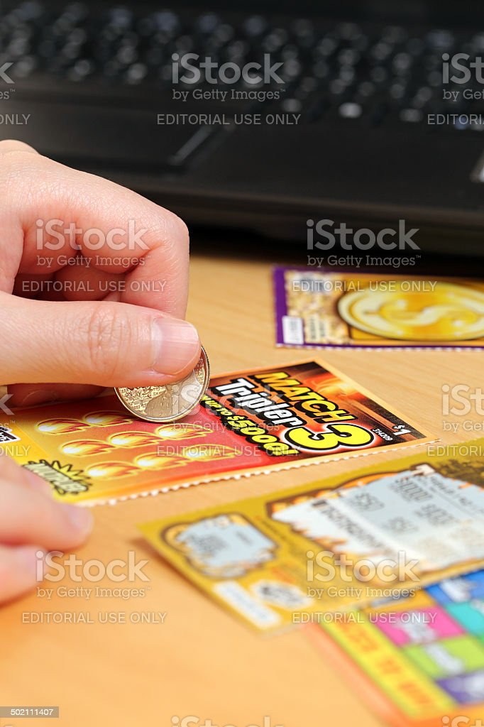 Woman scratching lottery ticket at home. stock photo