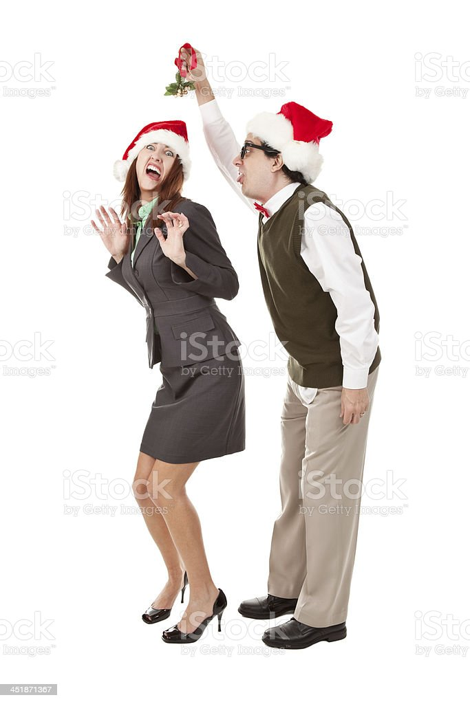 Woman Screaming As Nerdy Man Holds Mistletoe Over Her stock photo