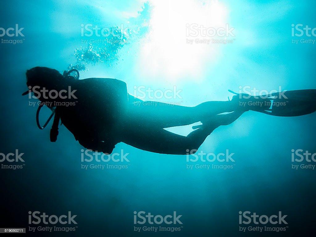 Woman Scuba Diving Under Sunburst stock photo