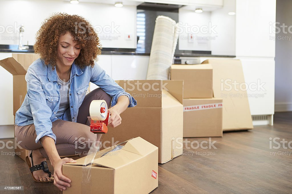 Woman Sealing Boxes Ready For House Move stock photo