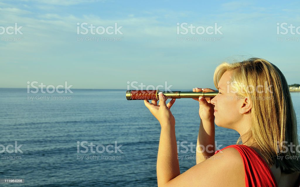 Woman Searches Ocean Horizon with Spyglass royalty-free stock photo