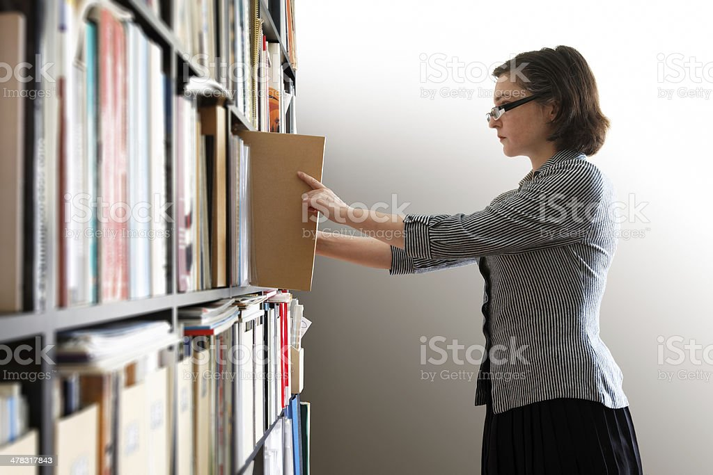 Woman searching a book in the library royalty-free stock photo