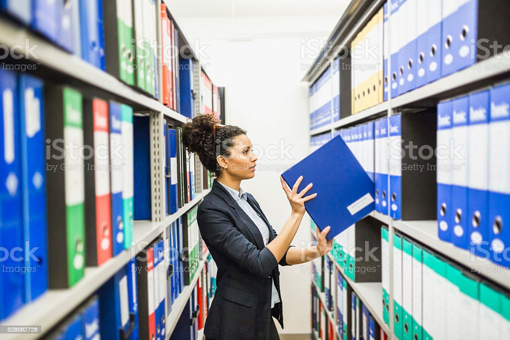 Woman searching for files in paper archive stock photo