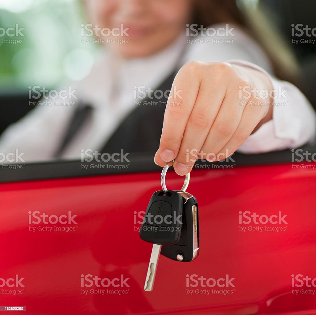 Woman seated in a car holding keys out the window stock photo