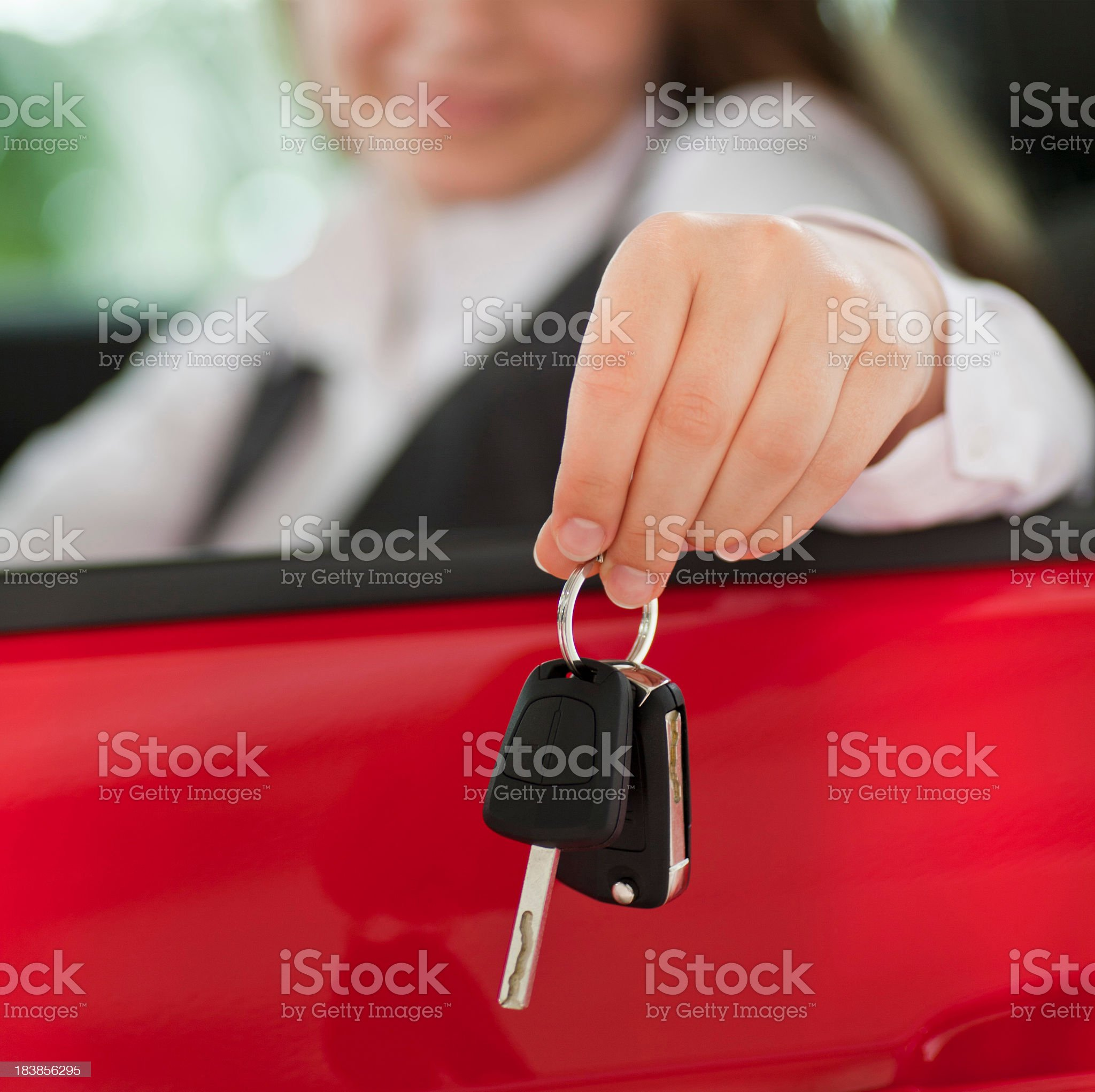 Woman seated in a car holding keys out the window royalty-free stock photo