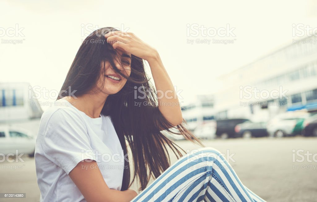 Woman seated on curb has her hair blown by wind stock photo