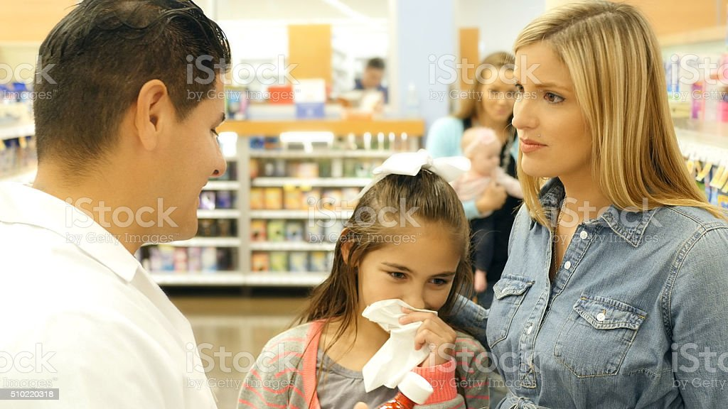Woman seeks advice from pharmacist in pharmacy stock photo