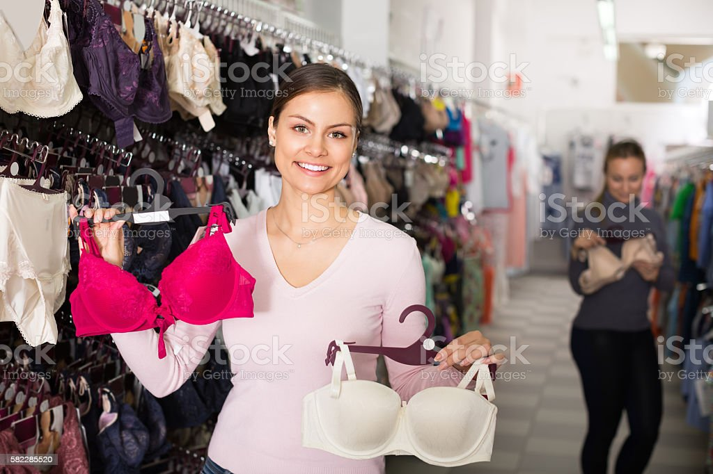 Woman selecting bra in lingerie store stock photo