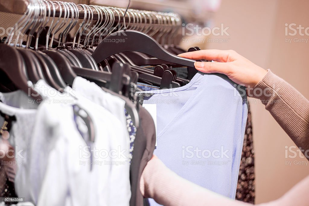 Woman selecting clothes in shop stock photo