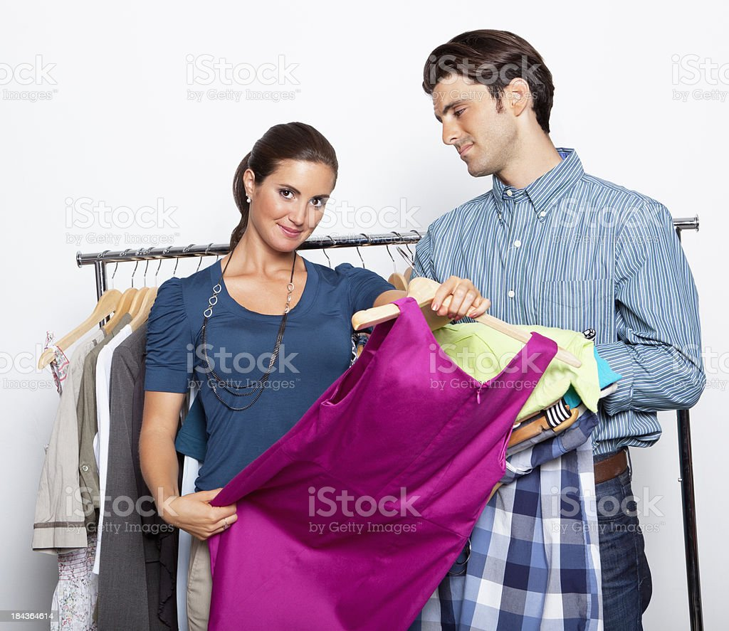 Woman selecting clothes with a guy at clothing store royalty-free stock photo