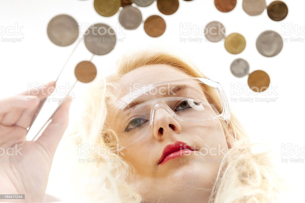 Woman selecting coins with tweezers stock photo