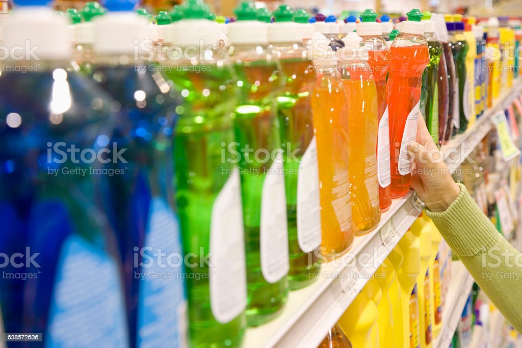 Woman selecting dishwashing liquid product in supermarket stock photo
