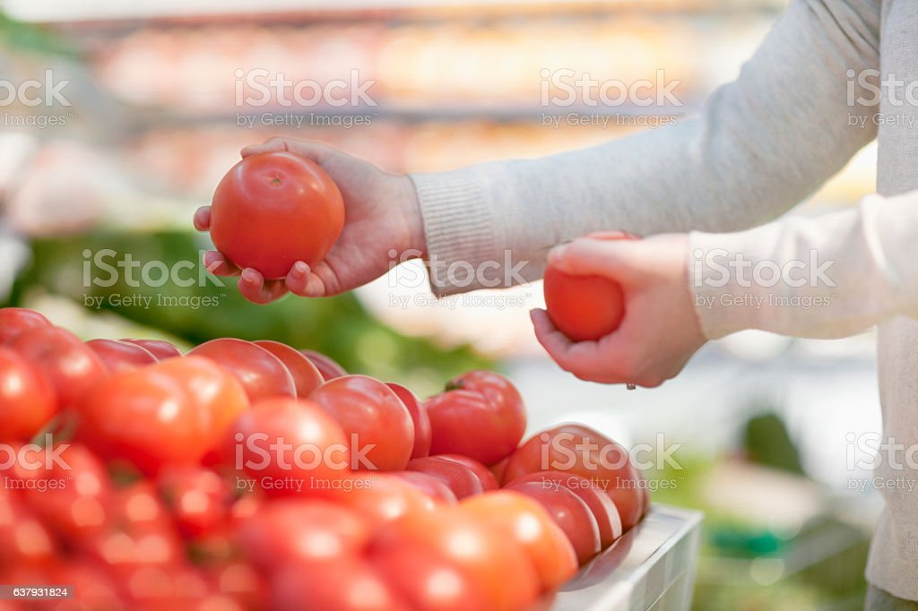 Woman selecting tomatoes at grocery store stock photo