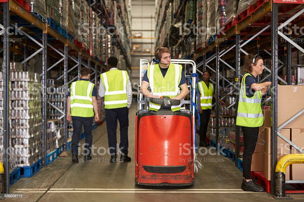 Woman selects box in warehouse for coworker on tow tractor stock photo