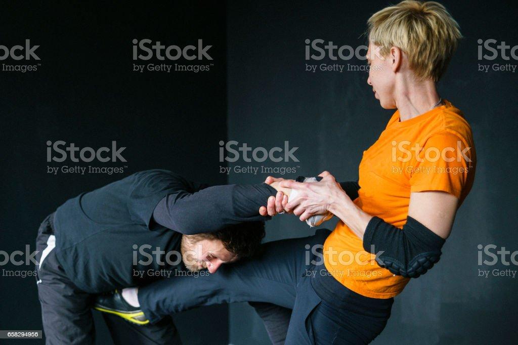 Woman self-defense trick against the man's attack. Strong women practicing self-defense martial art Krav Maga stock photo