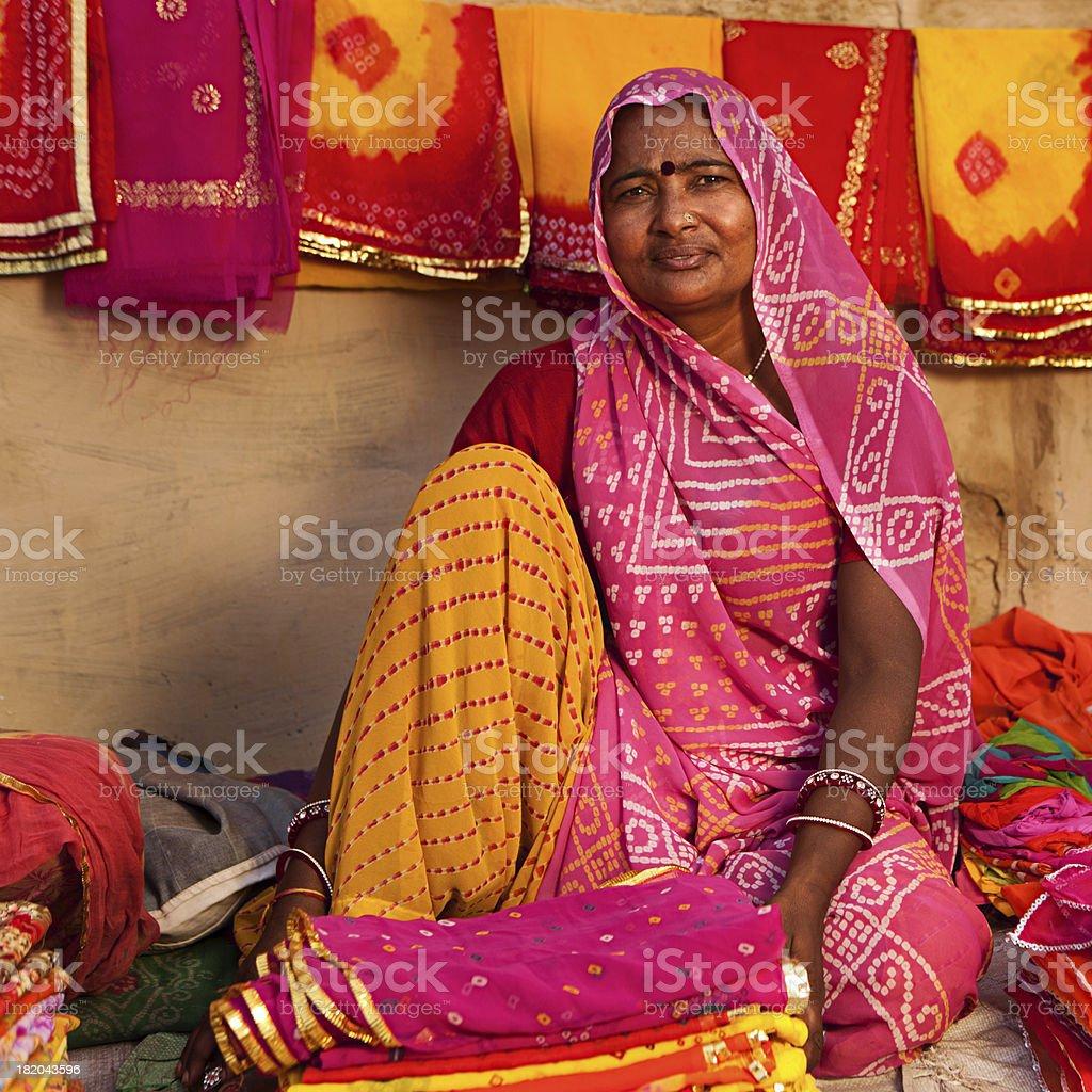 Woman selling colorful fabrics stock photo