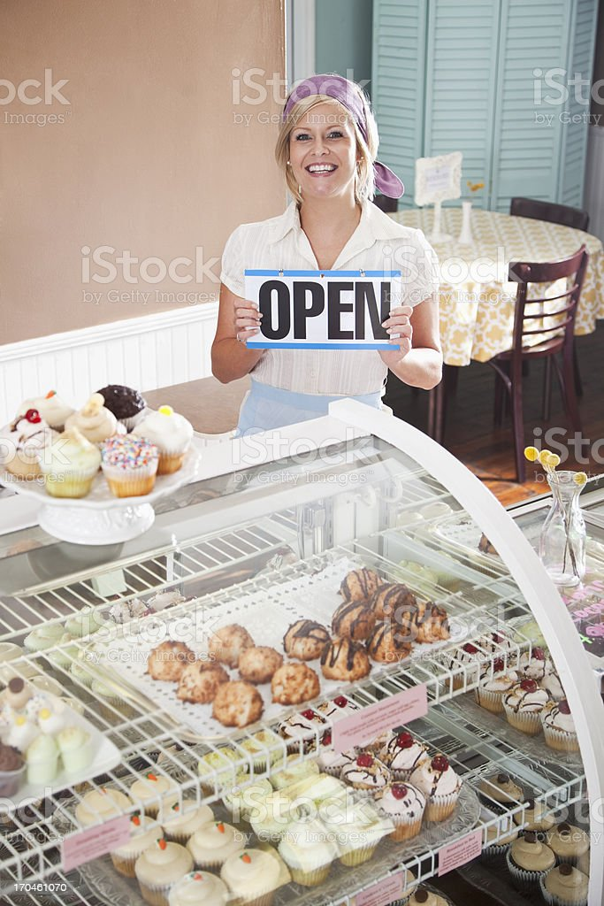 Woman selling cupcakes, holding open sign stock photo
