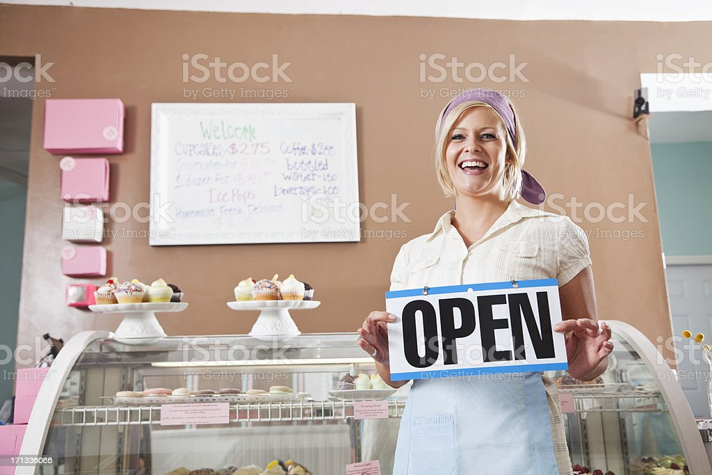 Woman selling cupcakes, holding open sign royalty-free stock photo