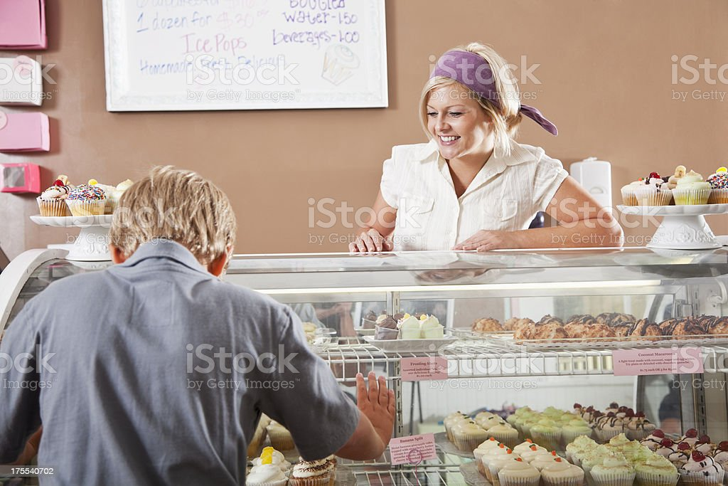 Woman selling cupcakes to boy stock photo