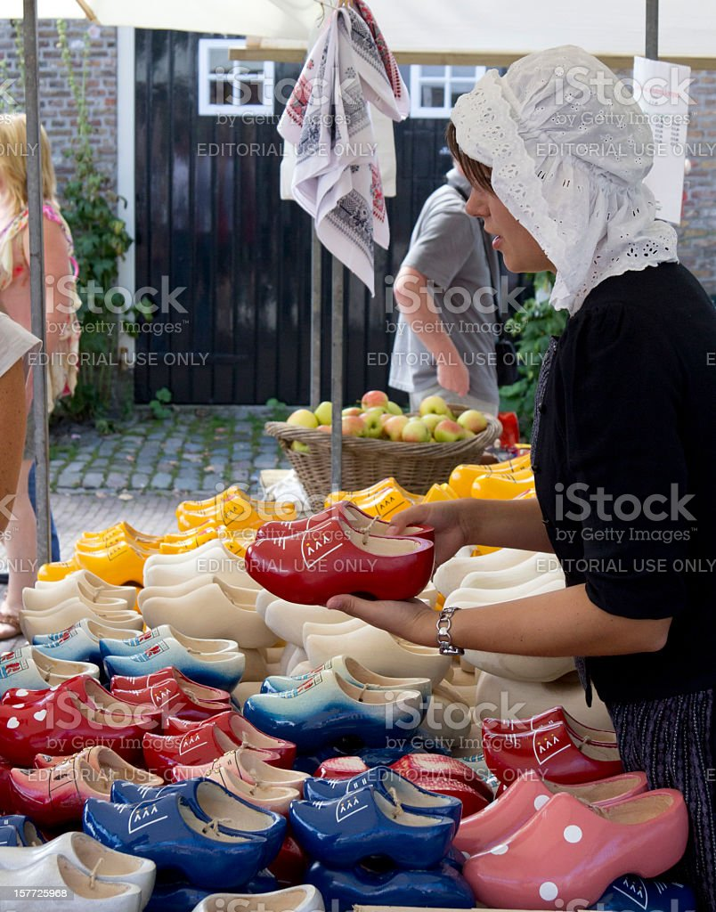 Woman selling Dutch clogs at a market stall stock photo