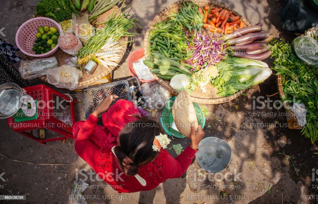 Woman selling fresh vegetables on the street market in Myanmar stock photo