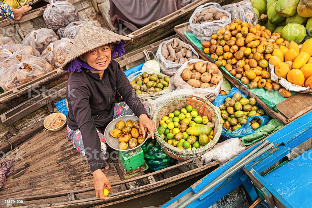 Woman selling fruits on floating market, Mekong River Delta, stock photo