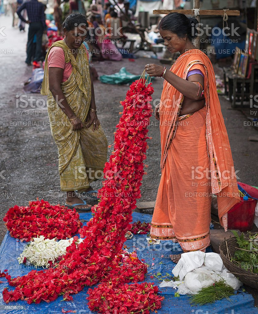 Woman selling garlands of Hibiscus, Kalighat, Kolkata, India. stock photo
