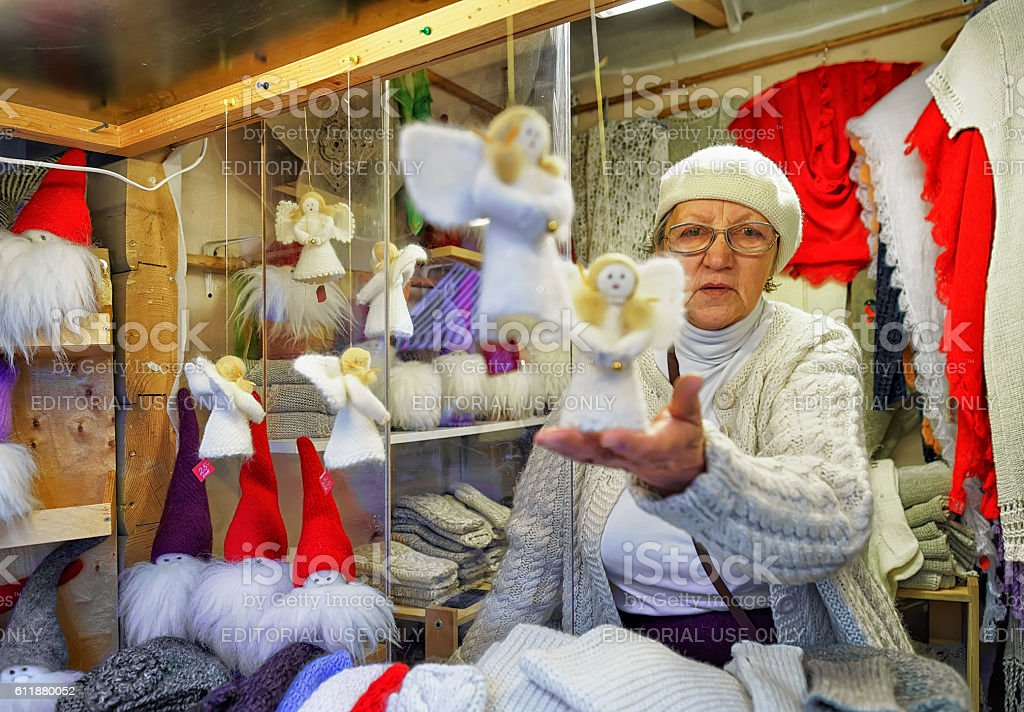 Woman selling handmade angel statues at Riga Christmas Market stock photo