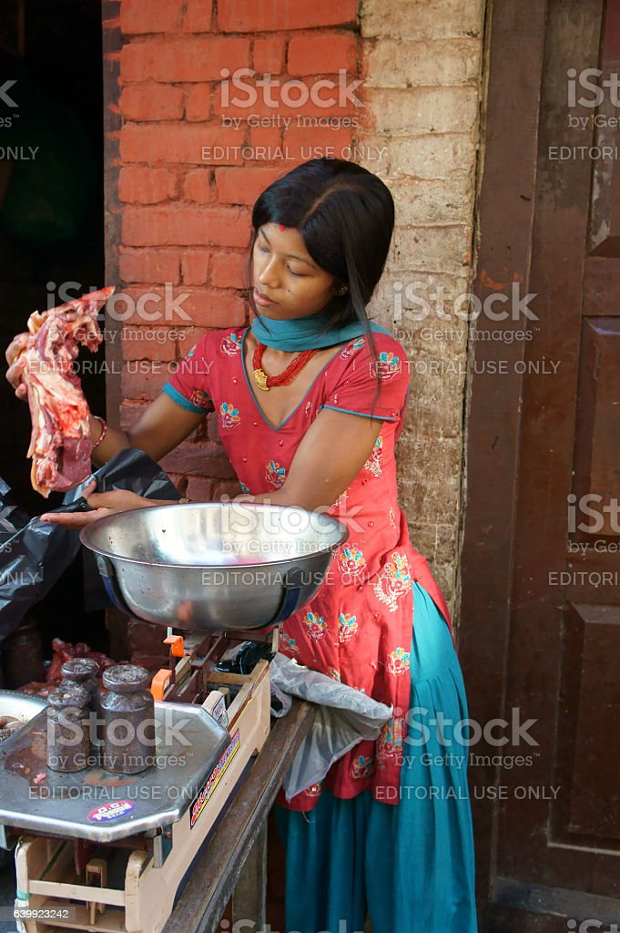 woman selling meat of a sacfrificed buffalo during dashein festi stock photo