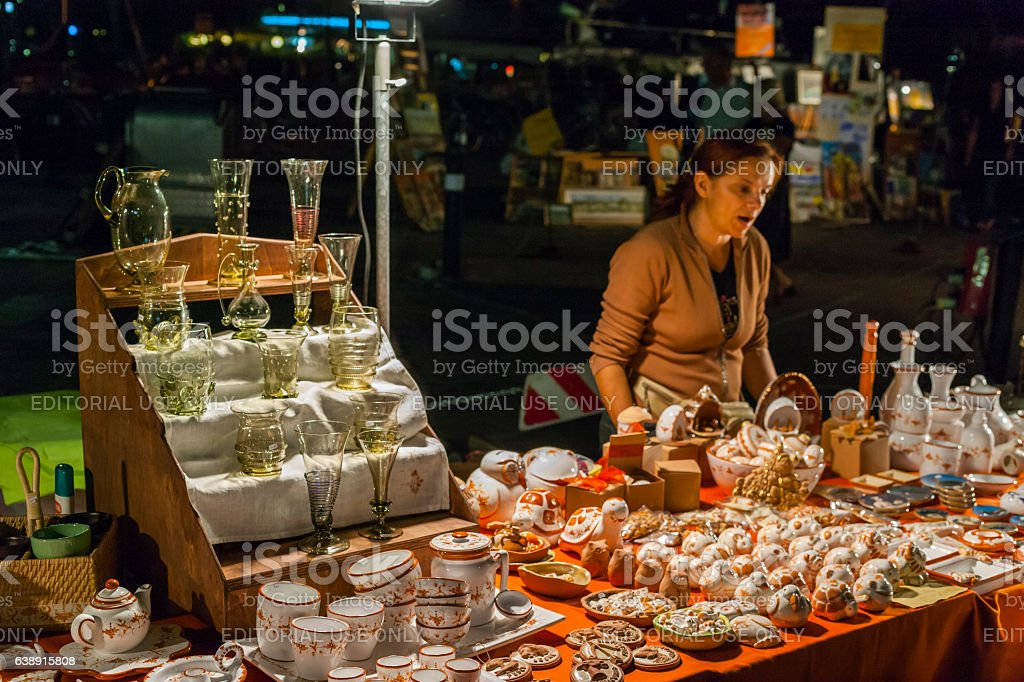 Woman selling pottery and glassware during a night market stock photo