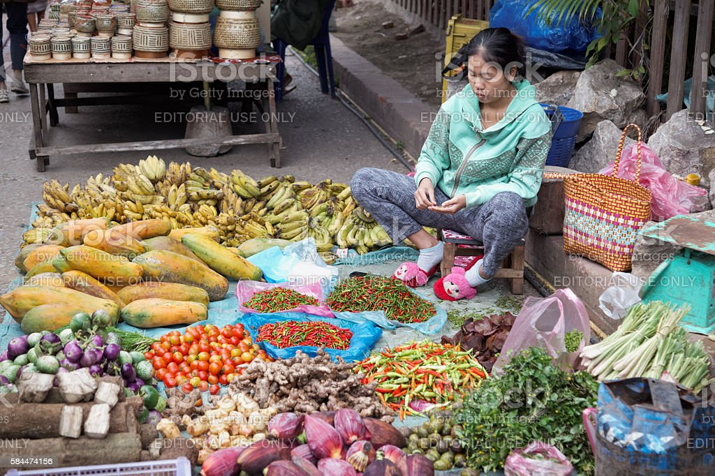 Woman selling vegetables in the market in Luang Prabang stock photo