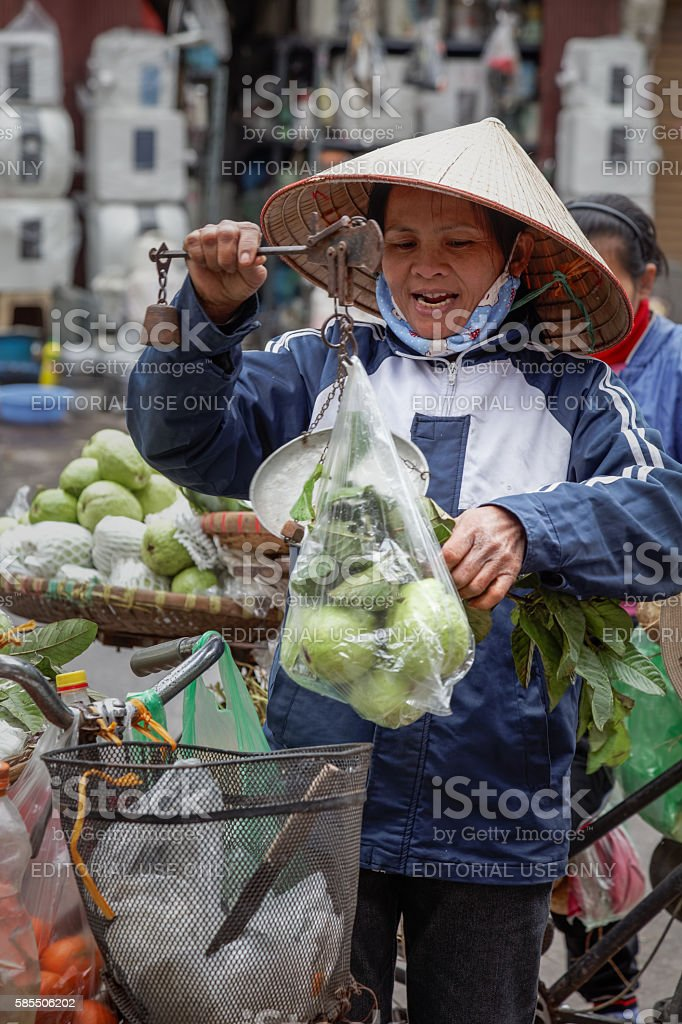 Woman selling vegetables in the street of Hanoi stock photo