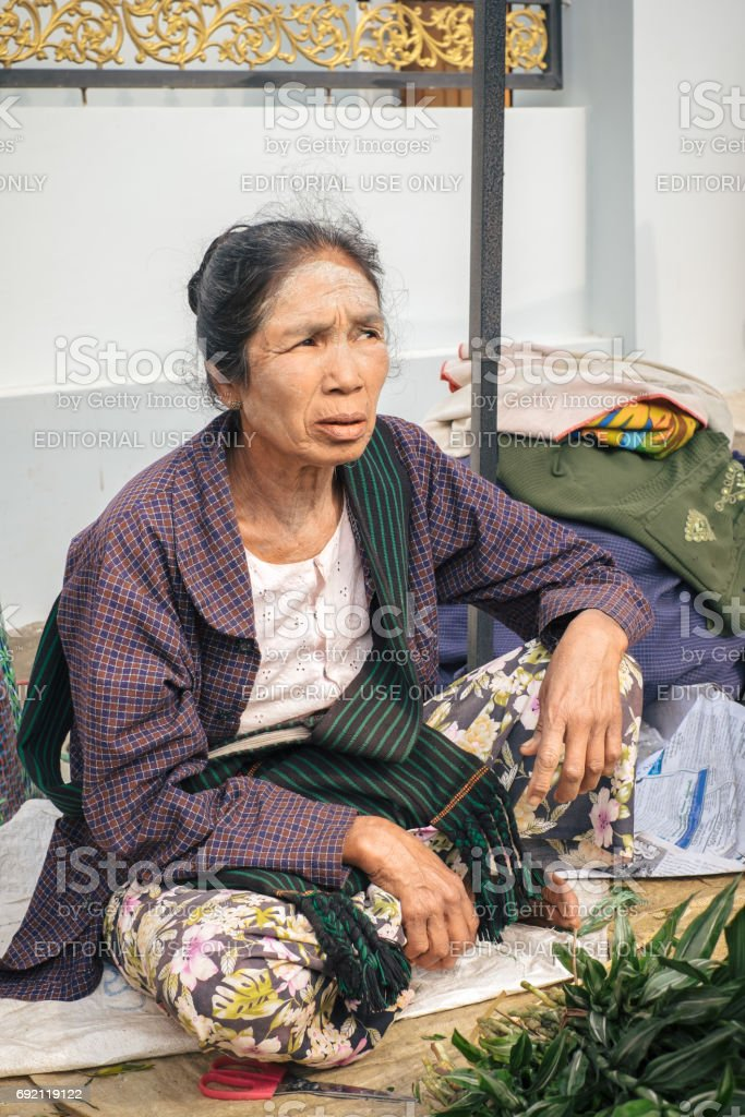 Woman selling vegetables on traditional street market in Myanmar stock photo