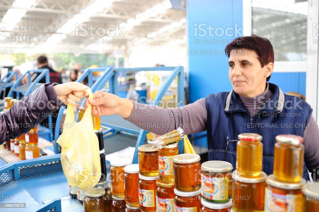Woman sells honey at Kardzhali farmer's market royalty-free stock photo