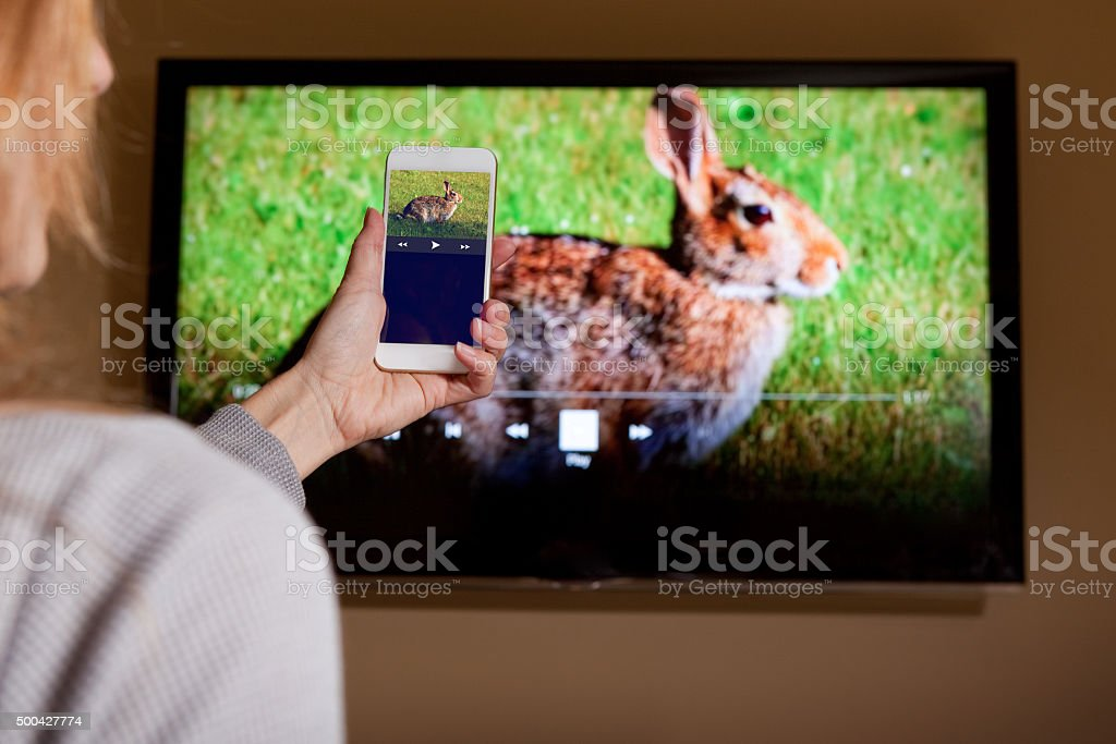 Woman Sending Video From Smartphone To TV stock photo