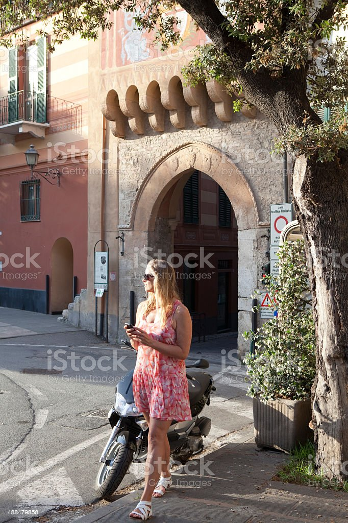 Woman sends text beside medieval entry stock photo