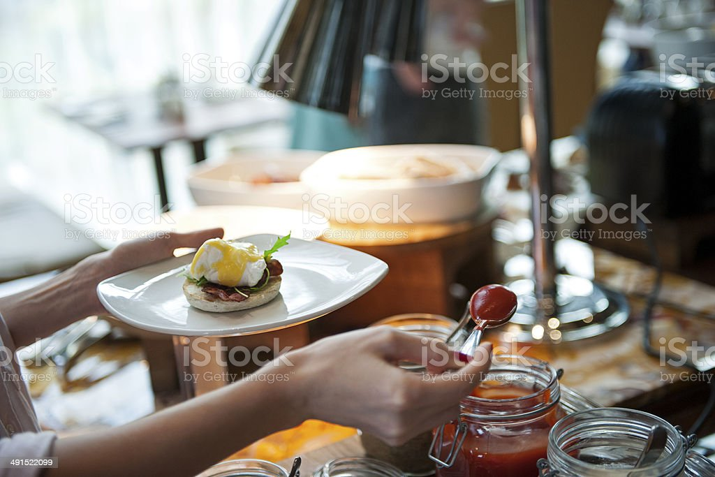 Woman serveng herself with eggs benedict breakfast royalty-free stock photo