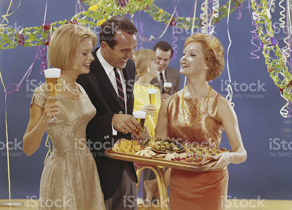Woman serving appetizers at party, smiling stock photo