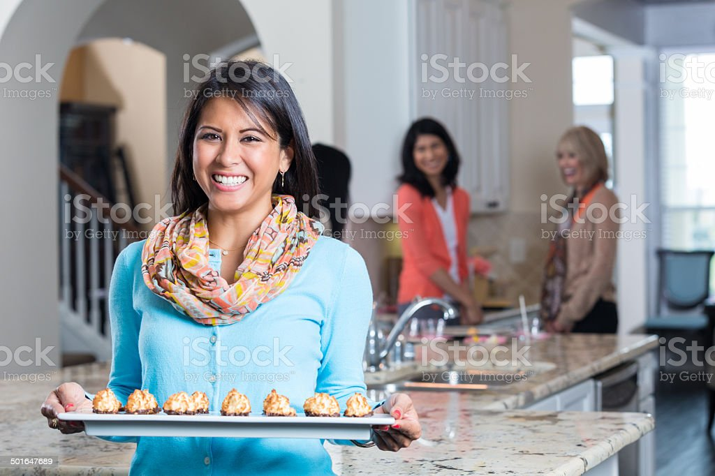 Woman serving appetizers to friends whle hosting sales party stock photo