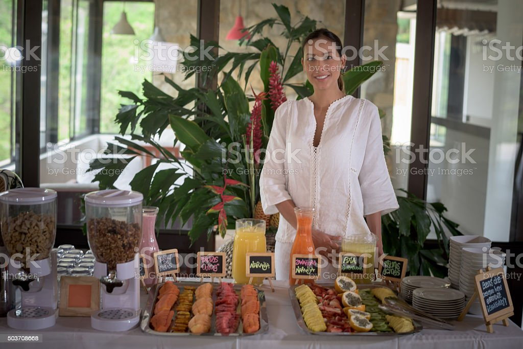 Woman serving breakfast at a hotel stock photo