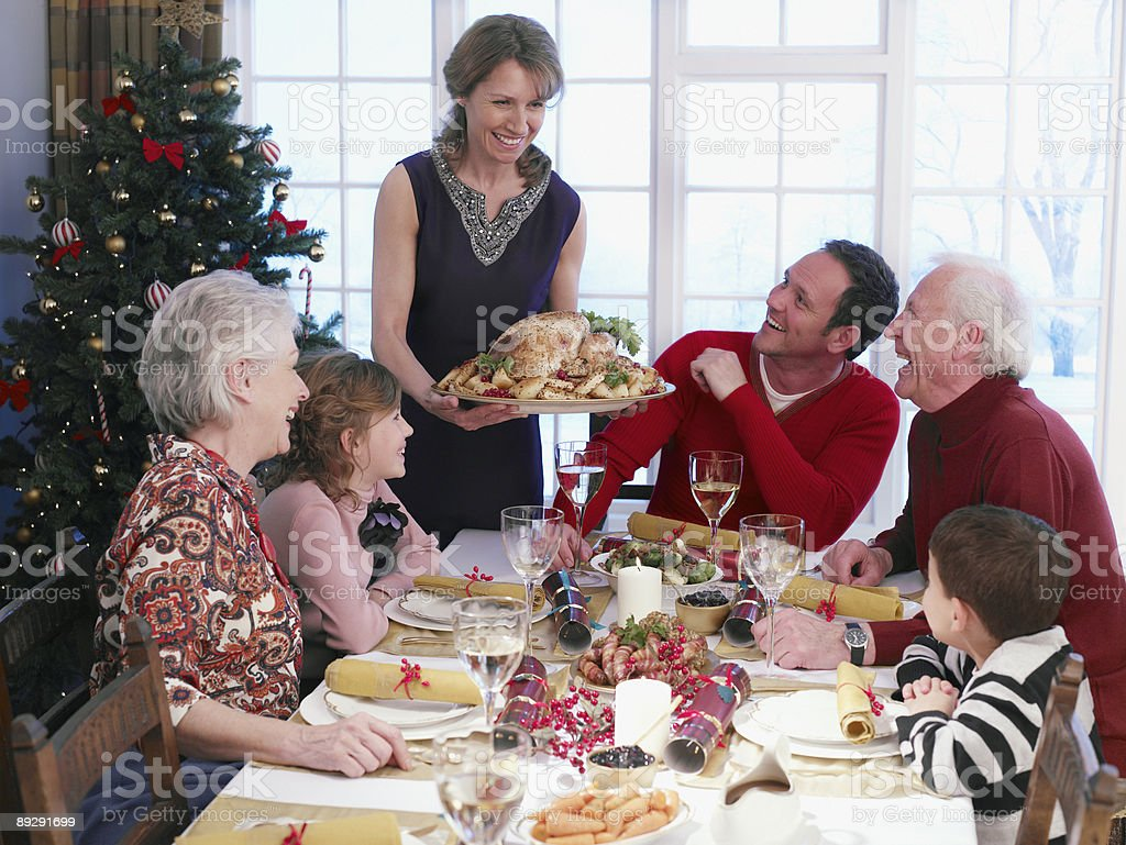 Woman serving Christmas turkey to multi-generation family at table stock photo